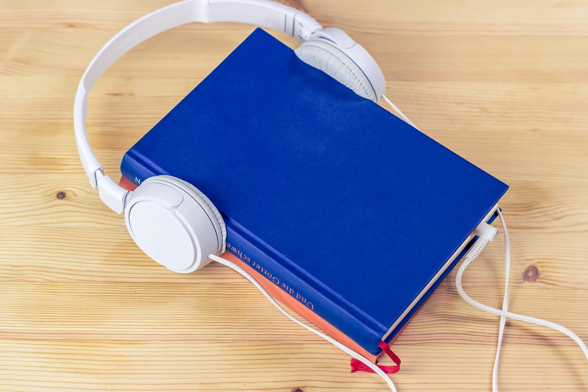 Auf diesem Bild sieht man ein Buch mit Kopfhörern, was die Audible Abo Kosten symbolisiert.